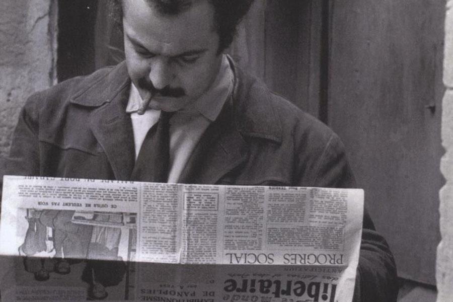 """Georges Brassens lisant le journal """"Le Libertaire""""."""